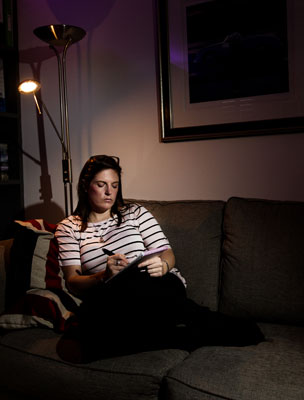 Alix King sitting on sofa writing in a notebook